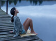 Serene woman sitting on dock over lake