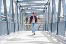 Young Man Walking On A Bridge ...