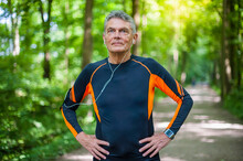 Confident Active Senior Man Standing With Hands On Hip At Park