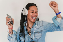 Portrait Of Dancing Woman Listening Music With Headphones And Smartphone