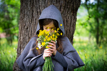 Girl Smelling On Bunch Of Yellow Wildflowers