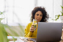 Woman Using Laptop At Desk In ...