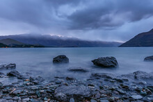 New Zealand, Otago, Cloudy Sky Over Rocky Shore Of Lake Wakatipu At Dawn With Remarkables In Background