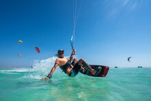 Kiter Does A Difficult Trick On A Background Of Transparent Water And Blue Sky