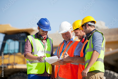 Photo Workers and businessman talking in quarry