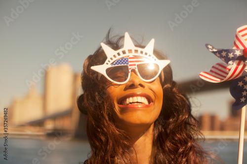 Fototapeta Woman with novelty sunglasses and pinwheel by urban bridge