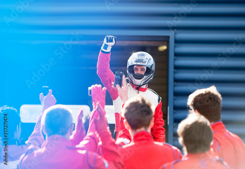 Fototapeta Racer and team cheering on track