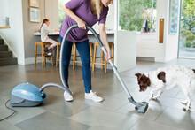 Woman Vacuuming Around Sleepin...