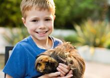 Smiling Boy Holding Guinea Pig Outdoors