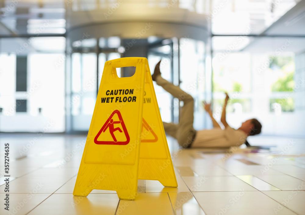 Fototapeta Businessman slipping on wet office floor
