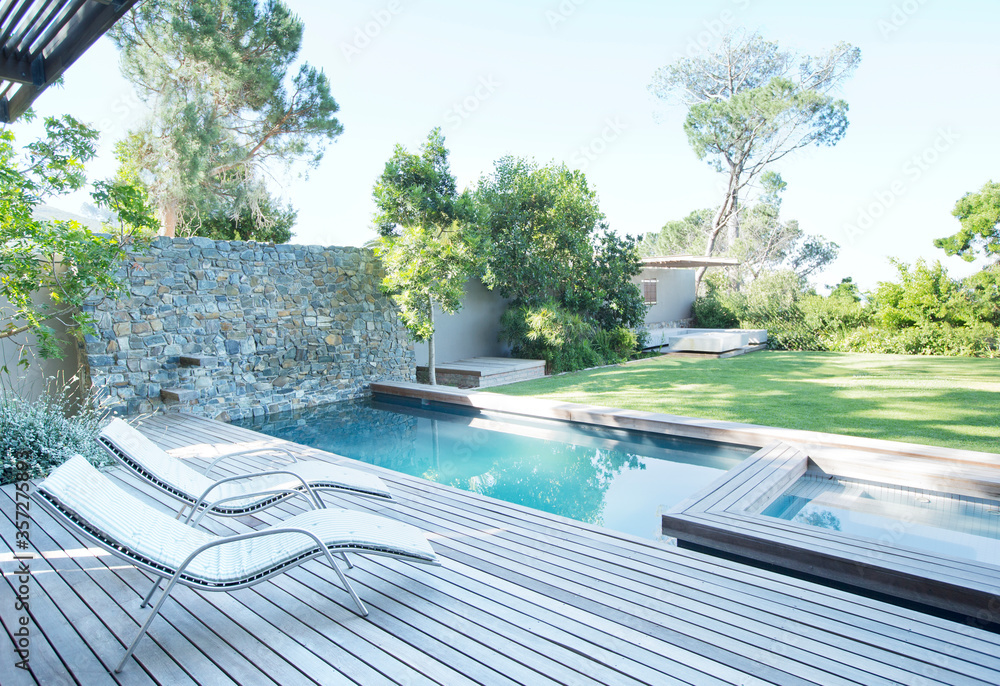 Fototapeta Lawn chairs and swimming pool in backyard