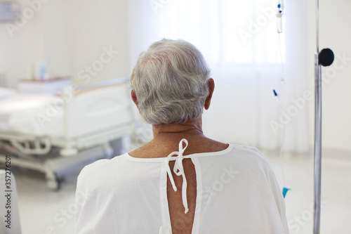 Older patient wearing gown in hospital room Canvas Print