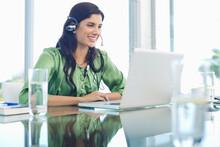Businesswoman Listening To Headphones At Desk