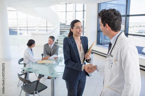 Doctor and businesswoman handshaking in meeting