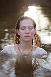 Serene woman with eyes closed in river
