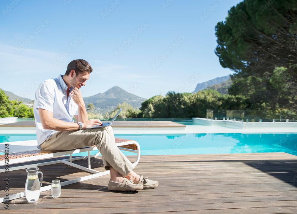 Fototapeta Man using laptop at poolside