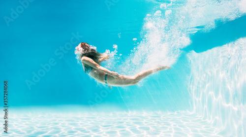 Obraz na płótnie Woman swimming underwater in swimming pool