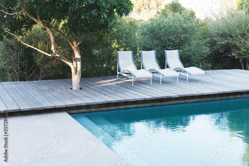 Photo Wooden deck and lounge chairs by swimming pool