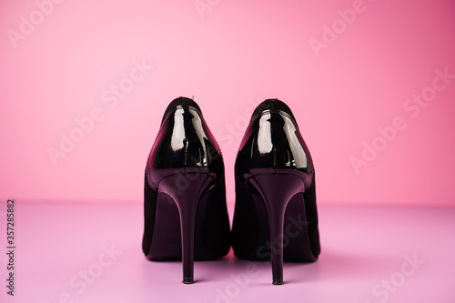 Obraz Close up of stylish black high heels shoes on a violet table with a pink background. - fototapety do salonu