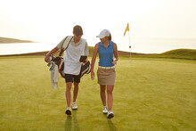 Golfer And Caddy Walking On Golf Course