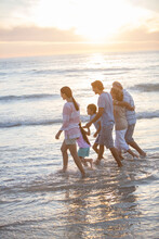 Multi-generation Family Walking In Surf At Beach