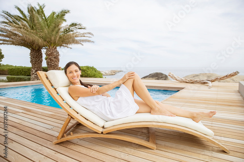 Valokuva Woman relaxing in lounge chair at poolside