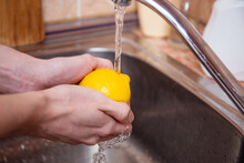 Hygiene, Health Care And Safety Concept - Close Up Of Woman's Hands Washing Lemon Fruit In Kitchen At Home.