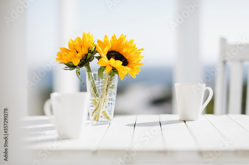 Foto Vase of flowers and coffee cups on kitchen table
