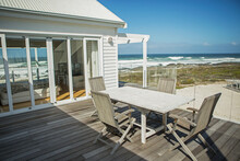 Table And Chairs On Balcony Overlooking Beach