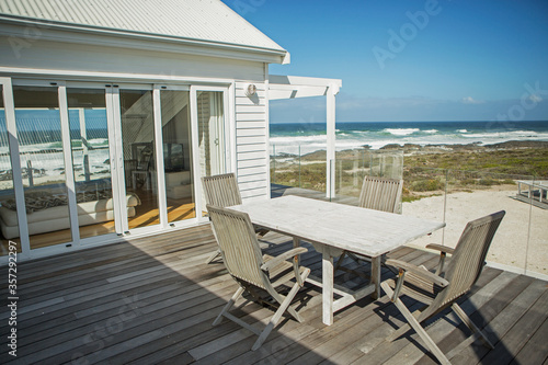 Fotomural Table and chairs on balcony overlooking beach