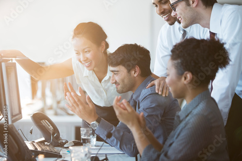 Business people cheering at computer in office Canvas Print