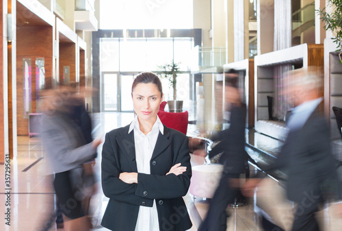 Photo Businesswoman standing in bustling lobby