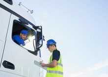 Worker With Clipboard Talking To Truck Driver