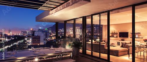 Fototapeta Illuminated modern living room and patio overlooking city obraz