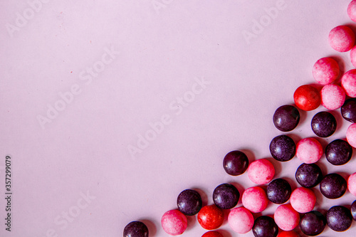 Violet background with round pink, purple and red candys on the right side. Top view with copy space