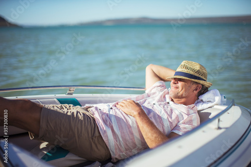 Fényképezés Older man relaxing in boat on water