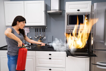Woman Using Fire Extinguisher ...