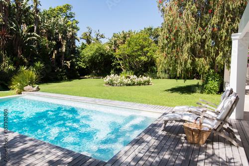 Obraz Lawn chairs overlooking backyard and swimming pool - fototapety do salonu