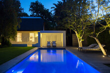 Lawn Chairs On Wooden Deck By Illuminated Swimming Pool At Night