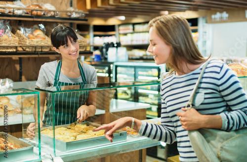 Vászonkép Clerk serving customer at deli counter in grocery store