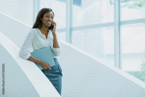 Businesswoman talking on cell phone on office building stairs Fotobehang