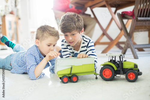 Fototapeta Brothers playing with toy tractor on floor