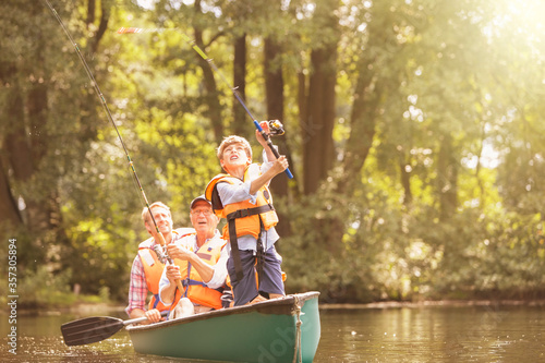 Canvastavla Boy, father and grandfather fishing from canoe on lake