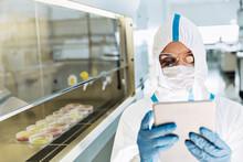 Scientist In Clean Suit Using Digital Tablet In Laboratory