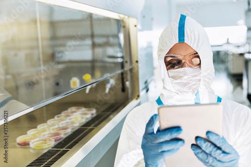 Slika na platnu Scientist in clean suit using digital tablet in laboratory
