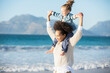 canvas print picture - Mother carrying daughter on her shoulders on beach