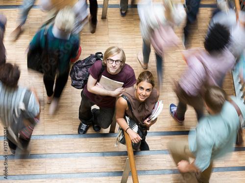 Fototapeta Male female students looking at camera standing in corridor during break