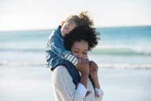 Mother Carrying Daughter On Her Shoulders On Beach