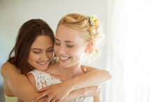 Bridesmaid Embracing Bride In ...