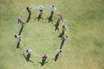 Team connected in circle by plastic hoops in sunny field